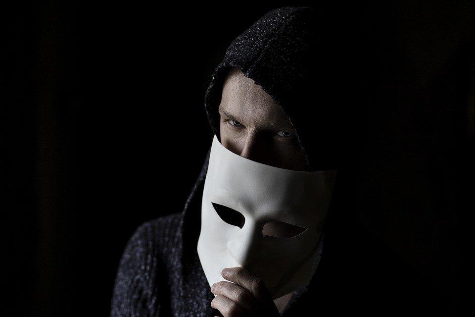 マスクを片手にほくそえむ男性